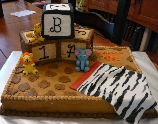 Chocolate baby shower cake with play blocks and jungle animals and zebra blanket