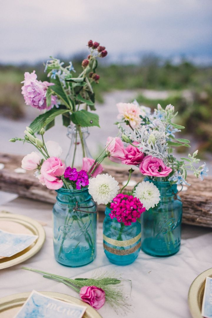 fuchsia-pink-and-cream-florals-work-beautifully-against-the-turquoise-mason-jar-vases.