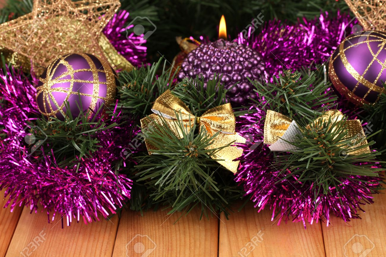 Christmas-composition-with-candles-and-decorations-in-purple-and-gold-colors-on-wooden-background-Stock-Photo