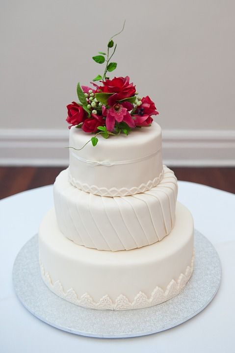 white vanilla wedding cake with red flowers