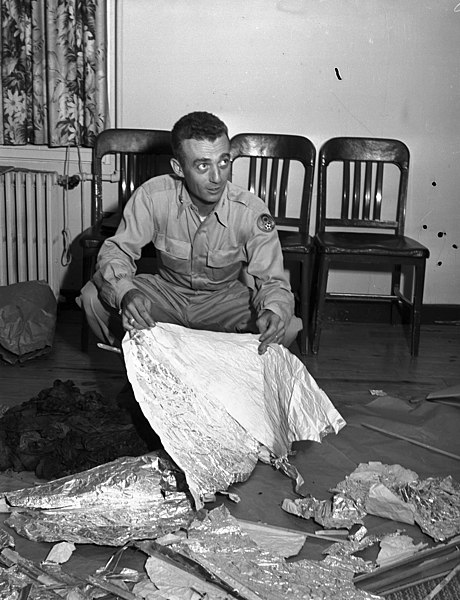 At Fort Worth Army Air Field, Major Jesse A. Marcel (looking left) of Houma, LA - holding foil debris from Roswell, New Mexico, UFO incident, 07/08/1947